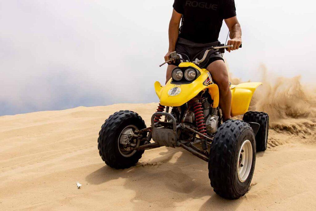 Person Riding Yellow ATV on Sand